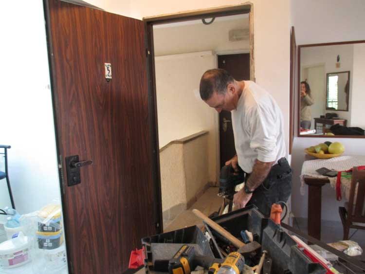 דלתות כניסה פלדלת. מנעולן בצפון בעבודה על משקוף הדלת
