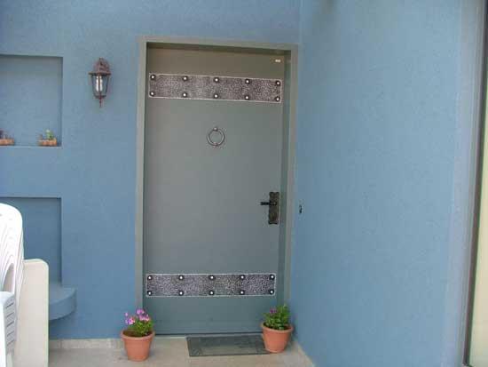 מתקין דלתות. דלת כניסה בצבע תואם לתכלת שבקיר